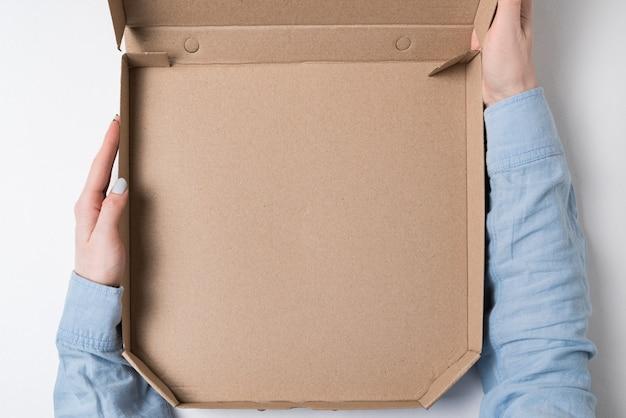 Mãos femininas segurar uma caixa de papelão vazia para pizza.