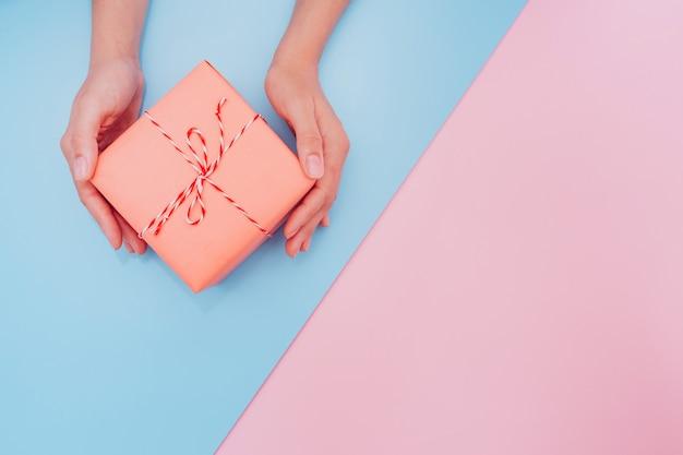 Mãos femininas segurar uma caixa de presente rosa com uma fita fina como um presente para o natal, ano novo, dia das mães ou aniversário em um fundo diagonal de mesa azul e rosa, vista superior. lugar para texto.
