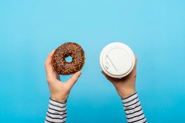 Mãos femininas segurar uma rosquinha e um copo de papel com café em um azul. loja de confeitaria conceito, bolos, café.