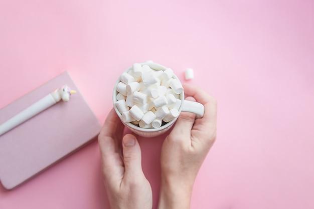 Mãos femininas segurar uma xícara de café com marshmallows com um bloco de notas e uma caneta de unicórnio. conceito de outono ou inverno. vista plana, vista superior