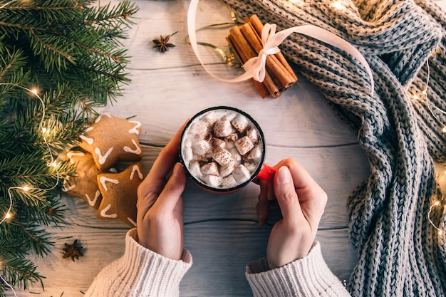 Mãos femininas segurar uma xícara de café ou chá em cima de um marshmallow. composição de bebida quente, biscoitos de gengibre e canela de natal ou ano novo. vista do topo.