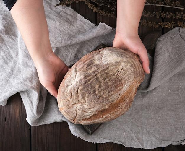 Mãos femininas, segure, um, inteiro, redondo, pão, de, pão centeio farinha