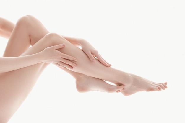 Mãos femininas sobre as pernas, conceito de cuidados do corpo de pele