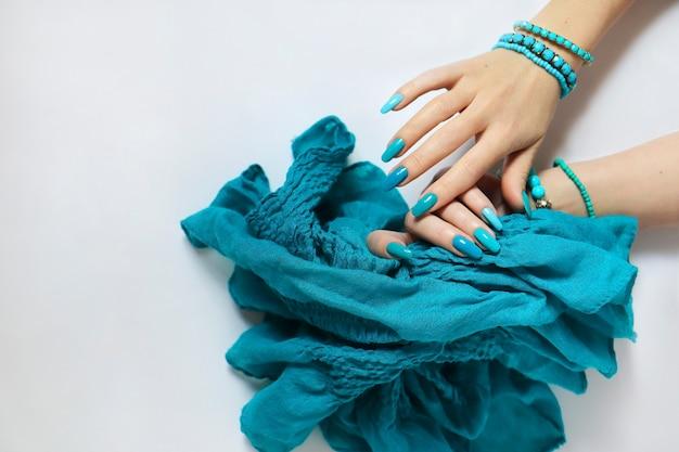 Mãos femininas sobre uma superfície clara com manicure azul e lenço