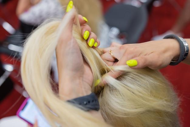 Mãos femininas tecendo um rabo de cavalo na cabeça das morenas