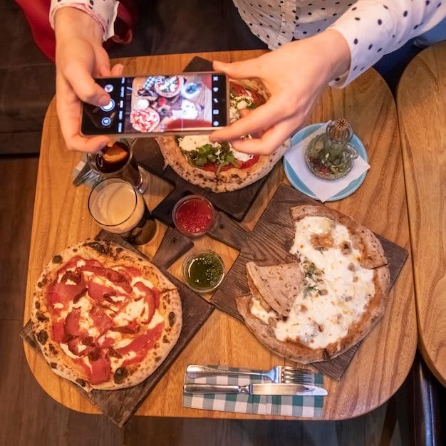 Mãos femininas tira fotos em uma mesa de smartphone com uma deliciosa pizza em um restaurante. vista do topo
