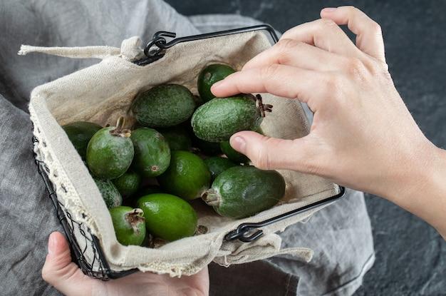 Mãos femininas tirando a fruta feijoa da cesta.
