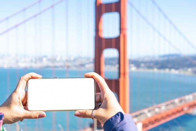 Mãos femininas tirando foto no telefone inteligente na frente do golden gate, conceito