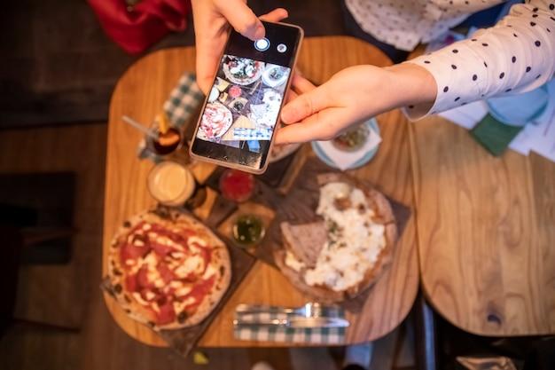Mãos femininas tirando fotos em uma mesa de smartphone com uma deliciosa pizza em um restaurante