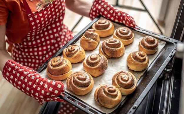 Mãos femininas tirando pãezinhos de canela cheirosos do forno quente