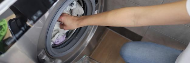 Mãos femininas tirando roupas limpas da máquina de lavar no banheiro
