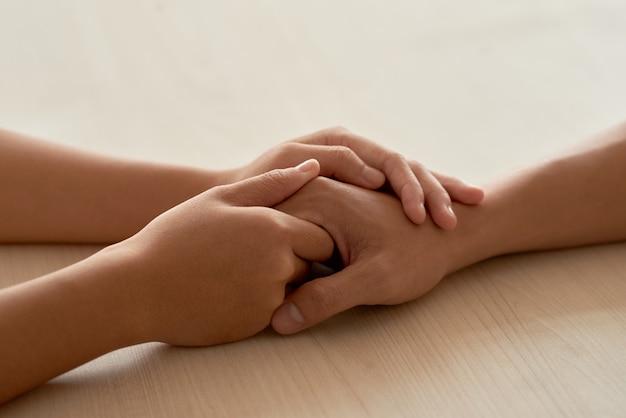 Mãos femininas tocando as mãos masculinas, tranquilizando o namorado