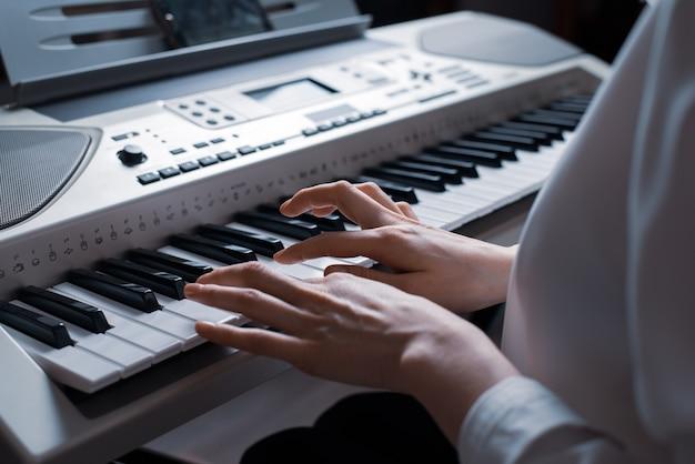 Mãos femininas tocando close-up do sintetizador