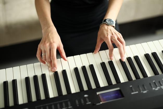 Mãos femininas tocando piano elétrico em casa
