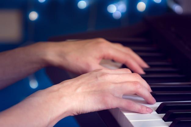 Mãos femininas, tocando, piano