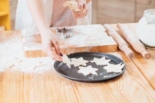 Mãos femininas trabalhando com massa para fazer biscoitos