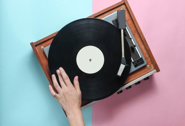 Mãos femininas usam jogador de vinil retrô em azul rosa pastel. dj. vista do topo