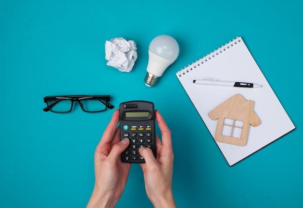Mãos femininas usam uma calculadora. cálculo econômico do custo da habitação.