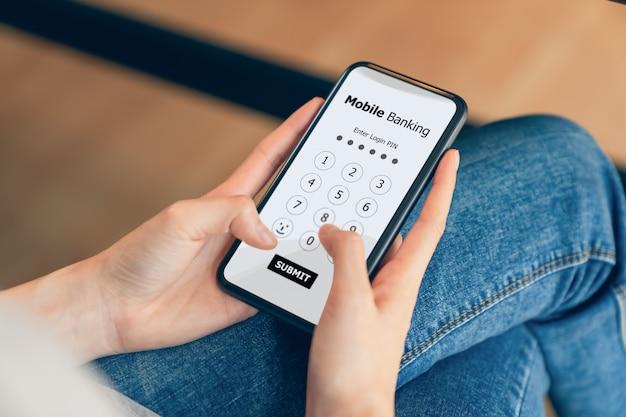Mãos femininas usando mobile banking no telefone e digite a senha para fazer login no aplicativo.