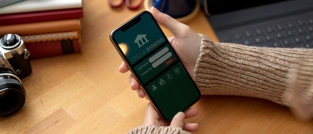 Mãos femininas usando o aplicativo bancário on-line no smartphone enquanto está sentado na mesa de trabalho