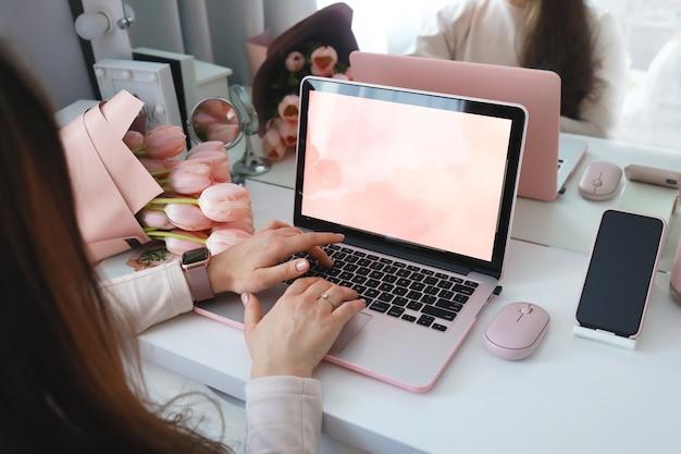 Mãos femininas usando o laptop. homeoffice do espaço de trabalho da mesa do escritório feminino simulado com laptop, buquê de flores de tulipa rosa, smartphone e acessórios cor de rosa.