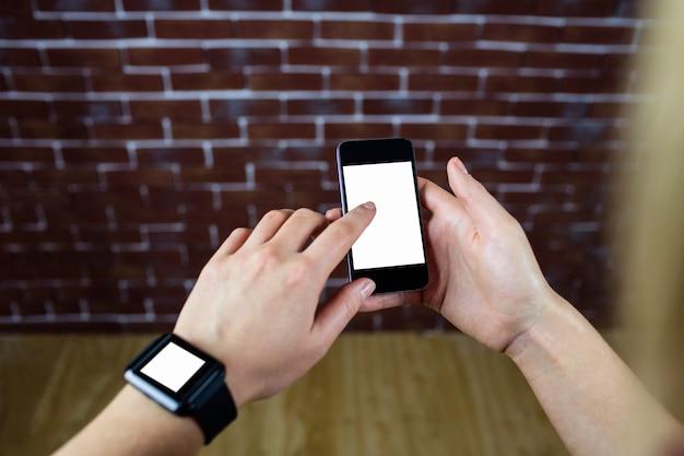 Mãos femininas usando smartphone e relógio inteligente