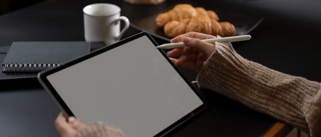 Mãos femininas usando tablet com caneta stylus na mesa do café da manhã com agendas, café e croissant