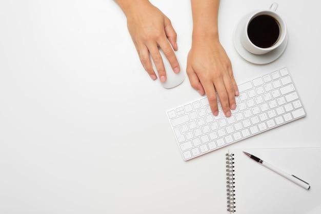 Mãos femininas usando teclado e mouse