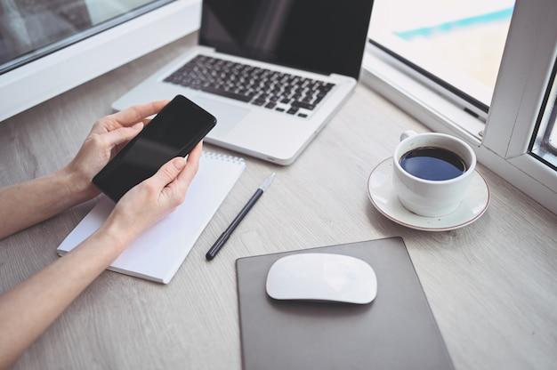 Mãos femininas usando telefone inteligente no local de trabalho interior, mulher de negócios freelance usando telefone celular na mesa de escritório, trabalhando em casa usando telefone inteligente e notebook. quarentena do trabalhador remoto