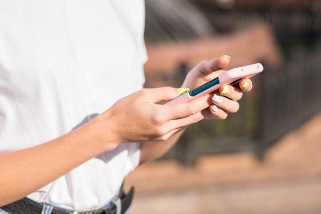 Mãos femininas usando um smartphone. conceito autônomo.