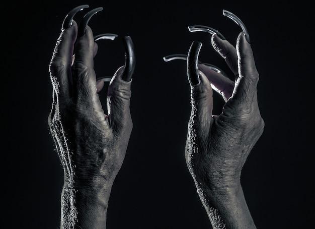 Mãos femininas velhas com unhas compridas