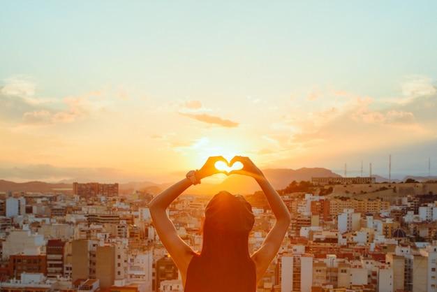 Mãos formando um coração ao pôr do sol