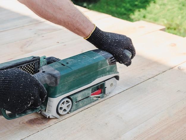 Mãos fortes de homens e uma máquina para trabalhar com madeira
