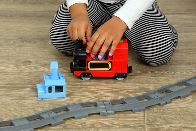 Mãos garotinha brincando com a ferrovia infantil