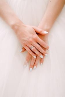 Mãos graciosas da noiva dobradas em uma saia fofa de um vestido de noiva closeup