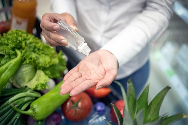 Mãos higienizando contra o vírus corona enquanto fazem compras no supermercado
