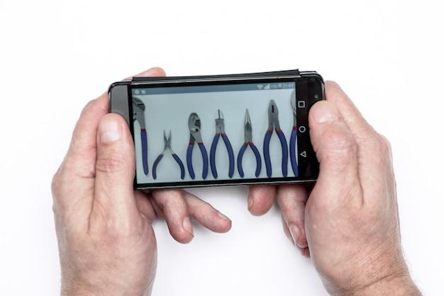Mãos homens segurando o telefone.na tela uma foto das ferramentas.