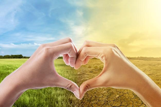 Mãos humanas com forma de coração contra as alterações climáticas no fundo