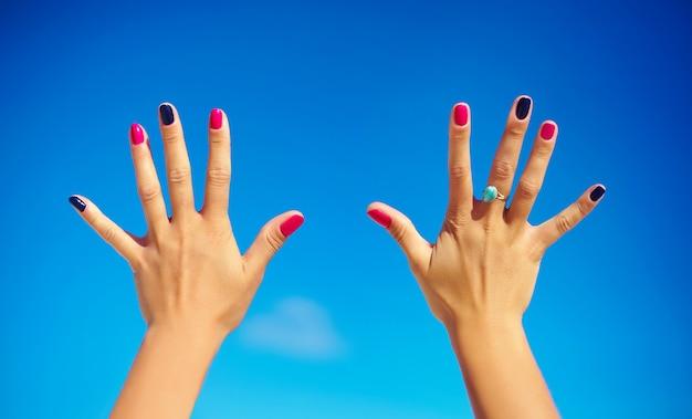 Mãos humanas com unhas coloridas brilhantes sobre o céu azul