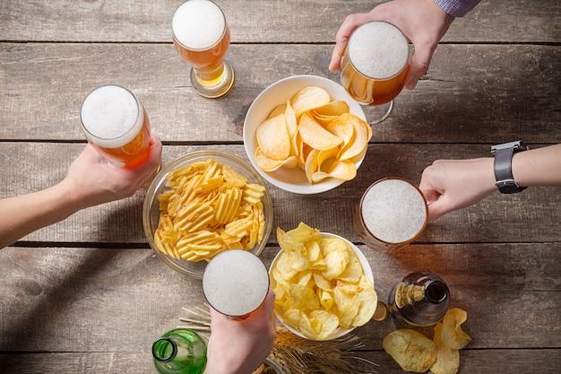Mãos humanas e copos de cerveja