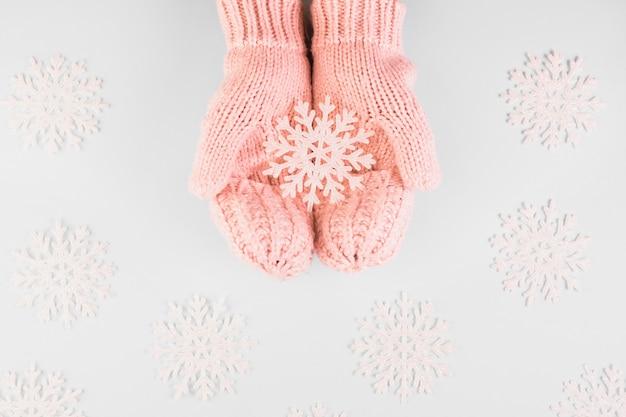 Mãos humanas em luvas com floco de neve de papel