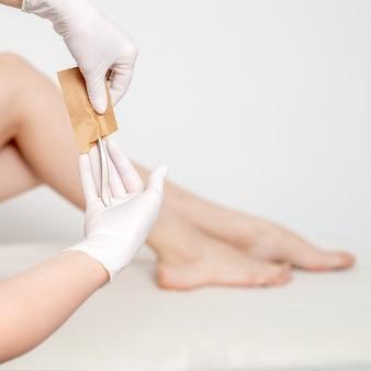Mãos humanas em luvas de proteção retirando ferramentas médicas ou de beleza do envelope de artesanato antes dos procedimentos