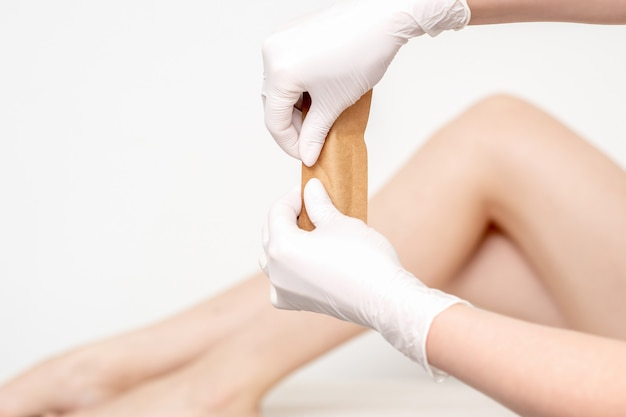 Mãos humanas em luvas de proteção segurando um envelope artesanal com ferramentas médicas ou de beleza nas pernas femininas