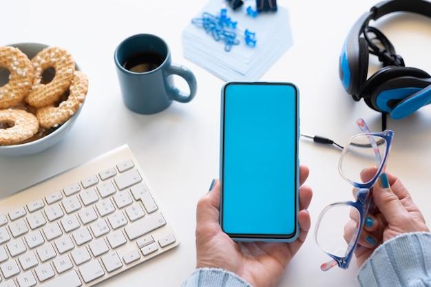 Mãos humanas femininas segurando um telefone inteligente e óculos em uma área de trabalho branca. cor azul nos acessórios