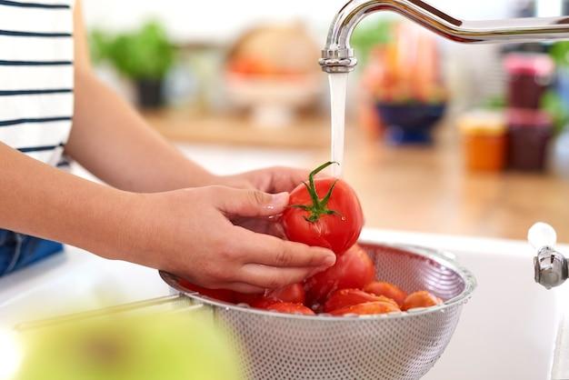 Mãos humanas lavando batatas frescas