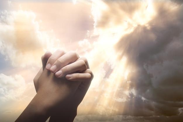 Mãos humanas levantadas enquanto orava a deus com um céu dramático
