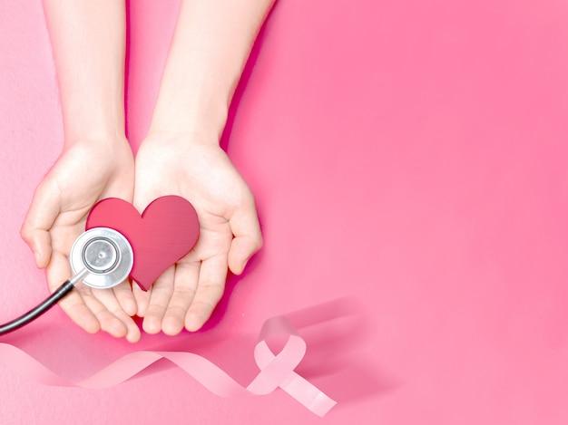 Mãos humanas, mostrando um coração rosa e estetoscópio com uma fita rosa