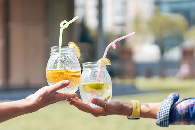 Mãos humanas no dia ensolarado de verão, bebendo um coquetel em potes de vidro.