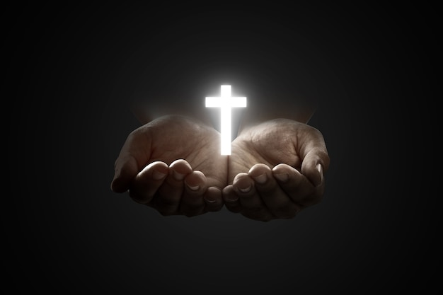 Mãos humanas orando a deus com a cruz cristã brilhante sobre fundo preto