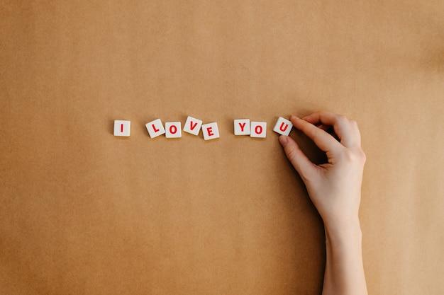 Mãos humanas, organizando eu te amo texto sobre fundo de papel kraft.